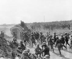 CAPTURE GREVILLERS NEW ZEALAND DIVISION 37TH DIVISION (Q 11262) Capture of Grevillers by New Zealand Division. Battle traffic at Grevillers 25 August 1918. Mark V (10th Battalion Tanks and infantry going forward captured 4.2 guns etc. (New Zealand and 37th Divisions).