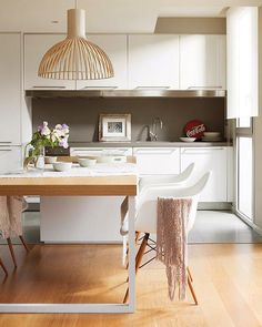 Victo 4250 in natural birch by Secto Design on top of a dining table in an apartment in Barcelona.
