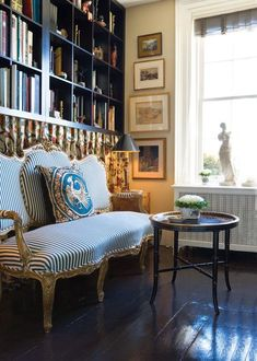 French-style library: Gilded settee, upholstered in a ticking stripe fabric.