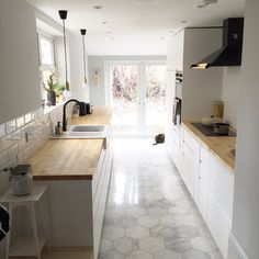 nice white and grey galley kitchen.  Like the pendant lights and wood countertops