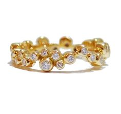 A playful take on the tradition of the eternity ring.  The irreverant pattern made by the linked bubbles all set with diamonds make it simple yet stunning.  18 carat yellow gold diamond eternity ring, diamonds total weight: .35 carat