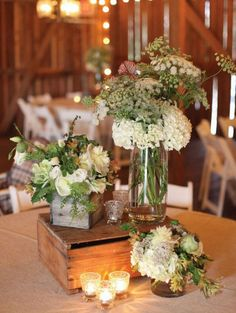 Rustic vintage inspired staggered height tablescape with a mix of arrangements in wood containers and different size mason jar arrangements.