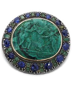 An antique malachite, emerald and sapphire cameo brooch, 19th century. Set to the centre with an oval malachite cameo carved to depict a stag with two putti surrounded by an elliptical frame of alternating oval-cut sapphires and square-cut emeralds, the lower half with oval-cut sapphires spaced by pairs of square-cut emeralds, mounted in silver and gold, later clasp, width 36mm. #antique #brooch