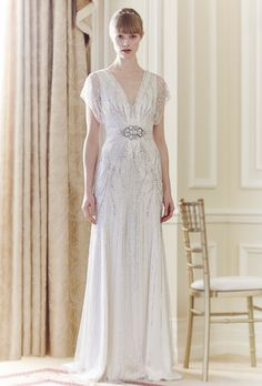 Brides: Jenny Packham. Floor length, beaded and tulle gown, with short sleeves, and sheath silhouette.