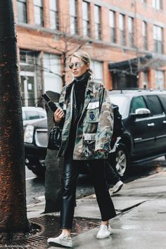 Camo utility jacket worn back with a roll neck sweater and cropped pants, finish…