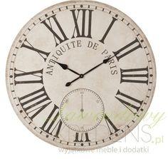 Jasnobeżowy, duży zegar w stylu prowansalskim o dużych cyfrach rzymskich i eleganckich napisach po francusku.