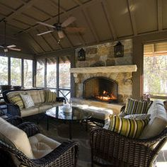 Screened porch with great stone fireplace by The Berry Group