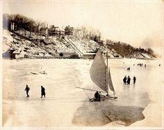 Ice boat and people on Hempstead Harbor, Bay Avenue neighborhood in background, 1906