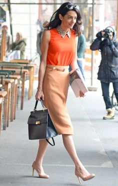 11 Chic Amal Clooney Looks to Inspire Your Work Wardrobe - The Columbia Law School visiting professor was snapped in New York wearing a sleeveless, snakeskin-collared orange Gucci top that she styled with a belted high-waist nude skirt, a chic Balenciaga top-handle