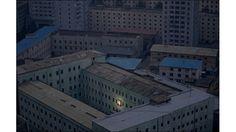 """""""  廃屋かと思うくらい、他の明かりはまったく見えません。  2012年の世界報道写真コンテストが行われ、受賞作品が発表されました。その中でも気になったのが上の写真です。これは北朝鮮の首都平壌で、金正日総書記死去の2ヵ月ほど前の2011年10月5日に撮影されたものです。  薄暗い画面の中で唯一光を放っているのは、金正日氏の父であり、北朝鮮の初代最高指導者であった金日成氏の肖像画です。街全体が、金日成像を輝かせるために持てるエネルギーすべてを捧げているようにも見えます。"""""""