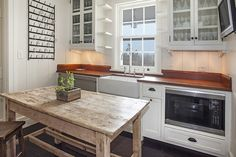 Cottage butler's pantry features glass-front upper cabinets flanking small corner shelves and window over a farmhouse sink and gooseneck faucet with stainless steel mini fridge next to stacked dishwashers to the left and a microwave to the right placed behind a farmhouse island.