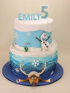 Two tiers of blue ombre vanilla cake with blue ombre fondant frills and hand made fondant moose and Olaf.