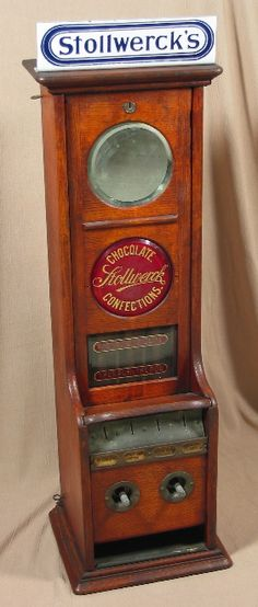 """Stollwerck L-Vendor (oak). Stollwerck, c. 1892, 32 1/4"""" (with marquee). Two ruby glass signs instead of a mirror and a sign. Chocolate Confections. Vending machine. Small Vintage Vending"""