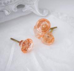 Mindre knopp formad som en rosa diamant. Med guld färgad metall stomme. Knoppen är av acryl dvs inte i glas, men den ser ut att