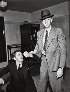 A reluctant suspect winces as a police officer takes things into his own hands, ca. 1934