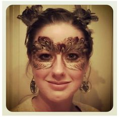 Owl makeup. (Did this myself using eyelash glue, feathers, regular makeup and acrylic craft paint. Put my hair up in two buns and added feathers to look like ears.)