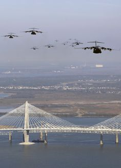 C17 Formation - US Air Force (USAF) C-17 Globemaster III Cargo Aircraft, assigned to the 437th Airlift Wing (AW) and the 315th AW, fly over the Arthur Ravenel Bridge, in Charleston South Carolina (SC), as part of the largest formation of aircraft deployed from a single base to demonstrate the US Air Forces strategic airlift and airdrop capabilities.