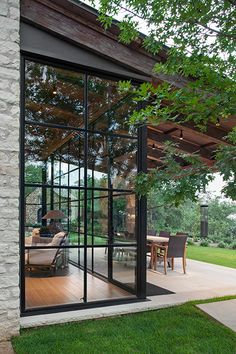Beautiful glass doors with black frames surrounding a traditional living room and leading out to a gorgeous tree-covered patio | Durango Doors