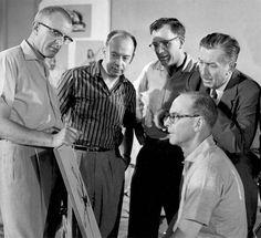 From circa 1957, Ollie Johnston (seated) with (l to r) Milt Kahl, Marc Davis, Frank Thomas, and Walt Disney. Photo courtesy Walt Disney Company