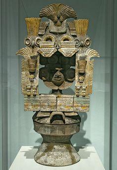 Teotihuacan Período clásico, 350 - 550 d.C. Arcilla, mica y pigmentos 72 x 34,5 x 24,2 cm Fundación Televisa  Este tipo de rostros como el que se halla en el medio con grandes aros en forma de discos representaban posiblemente a personas fallecidas. Se supone que los incensarios eran utilizados en ceremonias de purificación en los entierros.