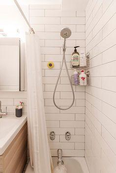 Serene bathroom renovation features Kohler shower fixtures and  Allegro white gloss shower tiles.