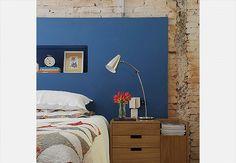 A cabeceira da cama é uma caixa de alvenaria rebocada e pintada com tinta acrílica fosca azul. Com 10 cm de profundidade, ainda foi possível aproveitá-la para fazer um nicho horizontal. O projeto é das arquitetas Paula Quatrocchi e Paloma Siqueira