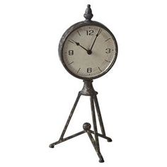 """$26 Distressed metal desk clock on a tripod stand.  Product: Desk clockConstruction Material: MetalColor: BronzeAccommodates: Batteries are not includedDimensions: 16.75"""" H x 7"""" Diameter"""