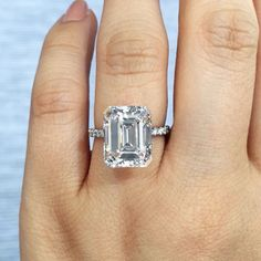 5ct emerald cut solitaire in platinum with diamond band.