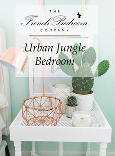 The French Bedroom Company   Urband Jungle Bedroom. We're loving the interiors trend of house plants - from concrete planters, cacti, basket pots, hanging plants, palms and so much green for your home. We love this white bedside with cacti and copper lamp with basket and light blue walls