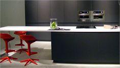 Donker grijze keuken met rode krukken aan het kookeiland