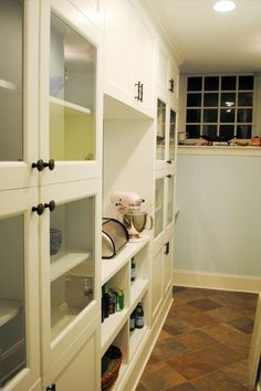 A combination of ready-to-assemble entertainment center cabinets were combined and trimmed with custom molding in this pantry to create both open and closed storage. thisoldhouse.com