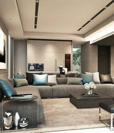 Sala de estar com sofá azul, almofadas azul e cinza, mesa de centro preta e rebaixo de gesso.