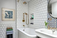 The upstairs bathroom includes a salvaged bathtub and sink from Demolition Depot. The blue-and-white Portuguese wall tiles above the sink are a vintage find from Solar Antique Tiles.
