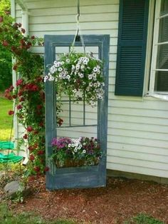 An old door is used in the garden as a plant holder display.