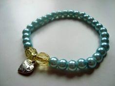 Bransoletka z niebieskich perełek z zawieszką.