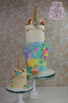 Two tier Unicorn cake with a baby Cake and cupcake. Buttercream and lots of glitter!