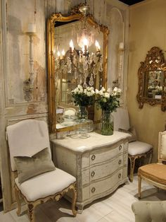 From Eileen Terwilliger's pinboard, full of gorgeous ideas for your home, worth a visit.  Shown - Beautiful antique off white chest and chairs with similar color upholstery, silver throw pillows, ornate gold mirror over chest, vase full of white flowers