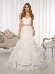 This fit and flare wedding gown of pure Regency Organza over Dolce Satin offers a superb fit with couture finishing. Crisscrossed Regency Organza ruching on the bodice flatters the figure, while layers of textured swirling Regency Organza with Diamante details on the skirt give this unique wedding dress a magical and airy feel.