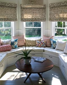 Lovely horse shoe shaped sunroom with Oly Studio Meri Drum Chandelier, built-in window seats with storage, white tufted cushion, pink & blue pillows, Reflections Canvas Pillow with Mirror Embroidery, round mid-century cocktail table and beige floral custom roman shades. (Bella Mancini Design)