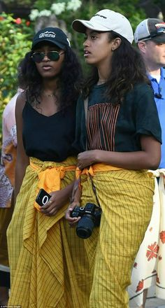 d72ad28f076 The Obama family  Life after the White House Sasha (L) and Malia Obama (R)  wore traditional yellow sarongs with sashes on their visit to the temple in  Bali.