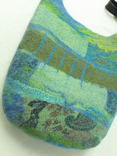 Nuno Felted collage hip bag with leather adjustable handle blues and greens. via Etsy.