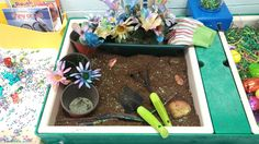spring sensory bin with real soil and seeds, garden tools and gloves, flower pots, sticks, stones, and fake flowers painted with water colors by the kiddos.