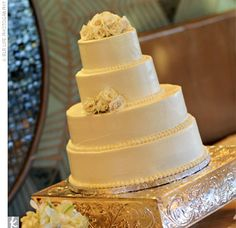 Guests indulged in a four-tiered confection with alternating layers of chocolate and carrot cake. A small bunching of white roses adorned the cake's top layer, and an accompanying bunch of roses was on the third layer. The cake sat on an embellished golde...