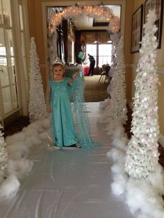 Frozen birthday decorations. White plastic on the floor, stuffing for snow and a few white Christmas trees and you have a grand entrance for your Frozen party.