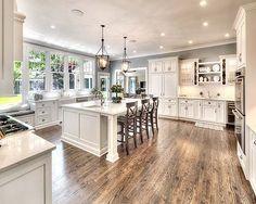 White kitchen. Farmhouse sink. Beautiful island. Lantern pendants. Love the windows infront of the kitchen sink.