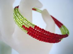 This is a Bright Red and lime green rocaille seed bead memory wire cuff bracelet. The bracelet expands to fit and is approximately 3 inches