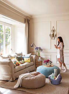 Mujer con taza se acerca a ventana en salón con sofá y pufs de tela redondos con cojines de flores 00368606