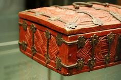 Casket dating from 1350 made of wood from a fruit tree and oak. The panels are nailed and banded together with bronze straps ending in rosettes. The box is carved and painted red.