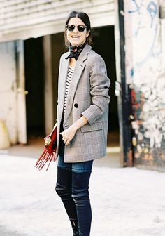 Leandra Medine wears a striped t-shirt, plaid blazer, jeans, leather boots, and a neckerchief