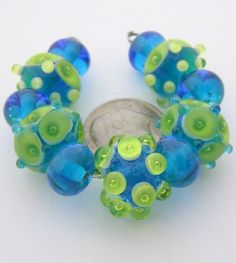 "Quantity: 11  Size: Approx. 6x9mm to 10x15mm (6mm = 1/4"")  Hole Size: 1-1/2mm made on 1/16"" mandrels  Colors: Clear, Dark Aqua, Lt. Grass & White    Eric's beautiful plunged-bubble & bubble-in-bubble beads in tropical Aqua & Grass for 'super cruise' fashion jewelry. Kiln annealed, carefully cleaned & thoroughly inspected for your beading pleasure in beautiful West Tennessee. Colors may vary from monitor to monitor. Please contact us if you are not pleased with your purchase. Happy customers…"